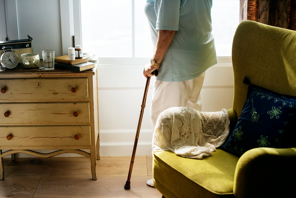 A picture of an elderly woman standing, holding a cane in an adult foster care room. A green chair and a wood dresser.