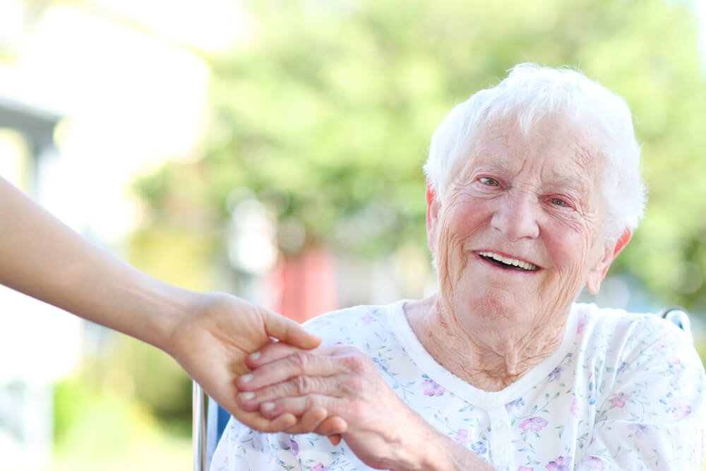 A picture of an elderly woman in a chair holding a young woman's hand.