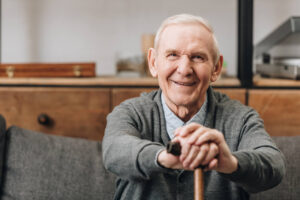 A picture of an elderly gentleman sitting down holding a cane.