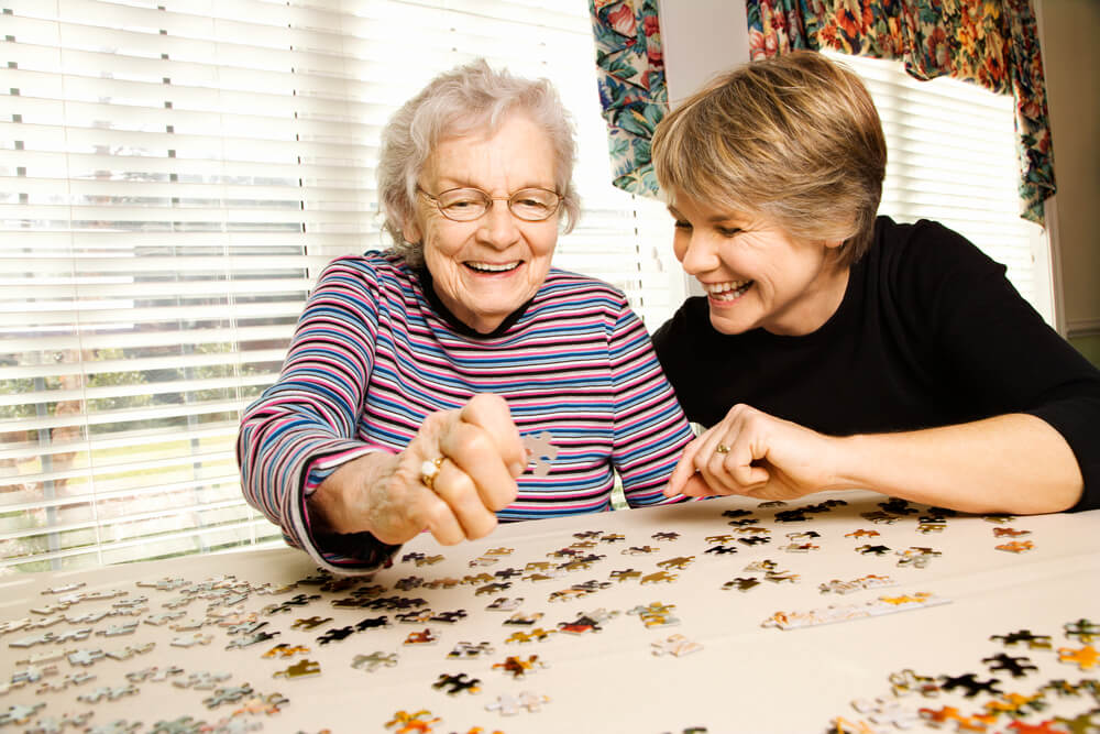 A picture of an elderly mom putting together a puzzle with her daughter.
