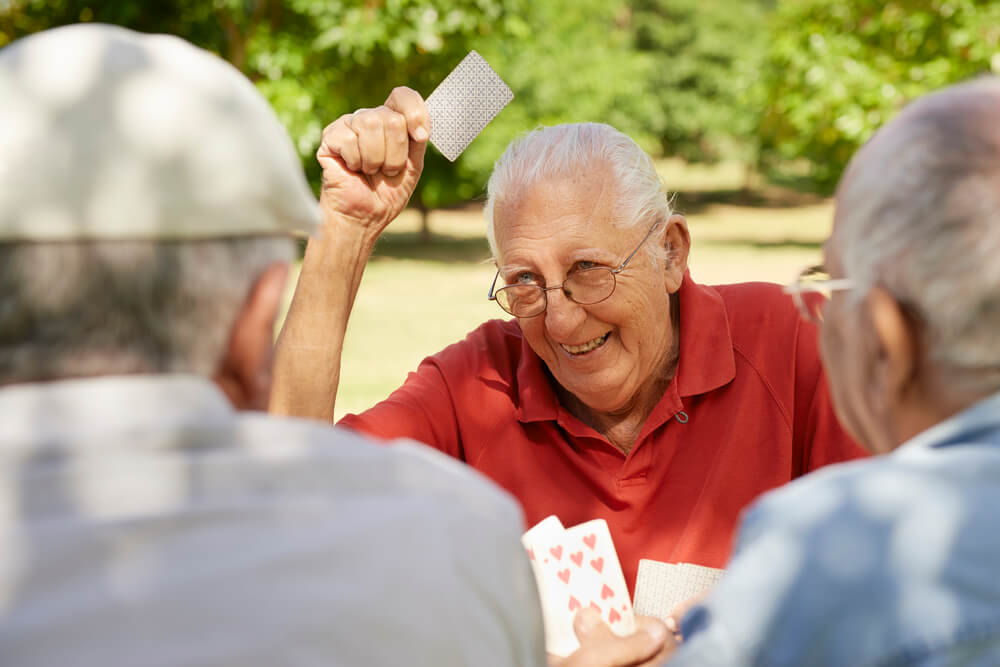 A group of elderly gentlemen playing card games.