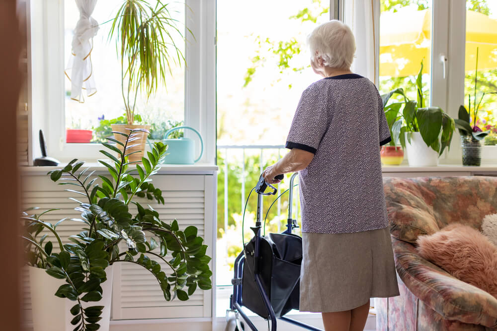 A picture of an elderly woman holding onto a walker in a room with some plants. Picture is used to depict an adult foster care home.